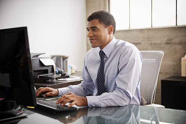 mixed-race-businessman-using-computer-in-an-office-G5BAEC7